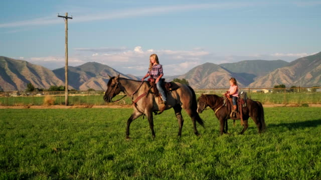 Young Cowboy Children with Horses Two young cowboy girl children with their horses on a ranch in Utah, USA. cowgirl stock videos & royalty-free footage