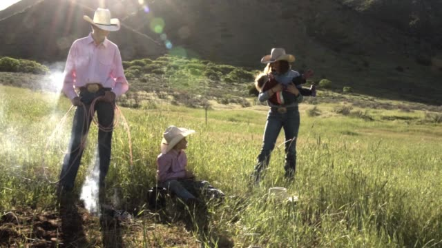 young cowboy family at campfire - ranch video stock e b–roll