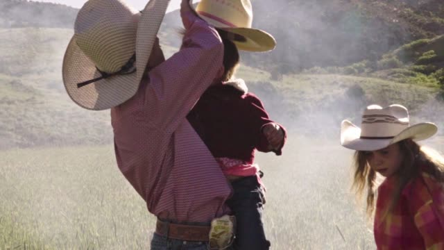 A Young Cowboy Places A Hat On A Little Buckaroo While A Young Girl Watches The Campfire
