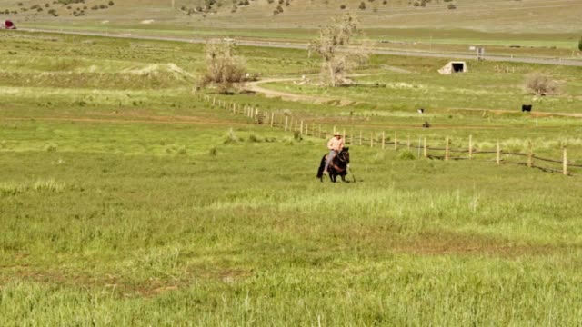 A Young Cowboy Riding His Horse Along A Fence Line Through The  Countryside Of Utah