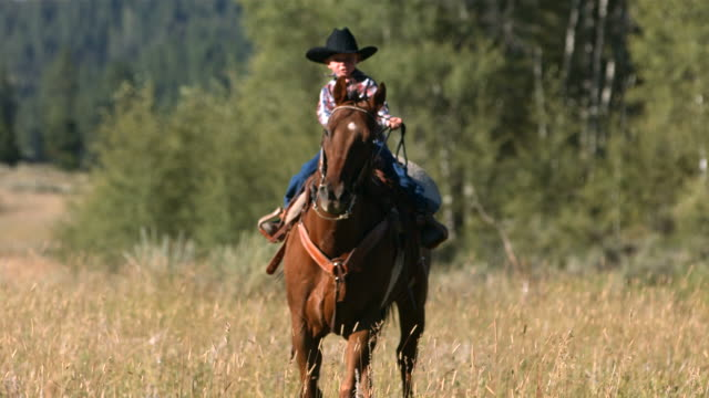 Young cowboy riding horse, slow motion video