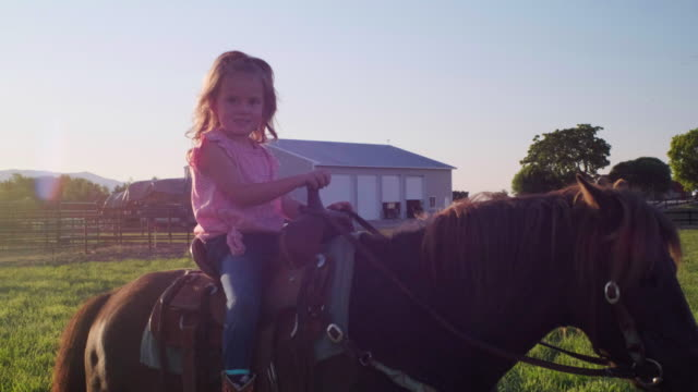 Young Cowgirl Riding Her Pony Horse A young cowgirl rides her pony horse on a ranch in Utah, USA. cowgirl stock videos & royalty-free footage