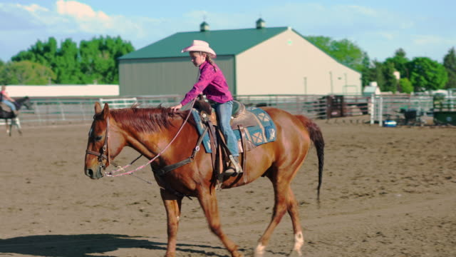 Young cowgirl riding horses on a ranch