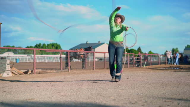 Young cowgirl training lassoing on a ranch in USA Video shot of cowgirl training how to lassoing on a ranch in rodeo arena in Utah, USA. She is holding and throwing lasso. Group of cowboys, cowgirls and horse are in the back. cowgirl stock videos & royalty-free footage