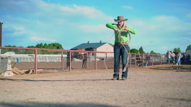 Young cowgirl training lassoing on a ranch in USA