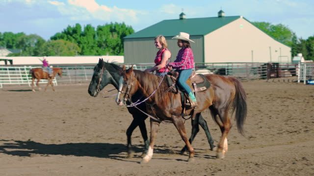 Young cowgirls riding horses on a ranch Group of young cowgirls is horseback riding in rodeo arena in Utah, USA. Sunlight in the back. cowgirl stock videos & royalty-free footage