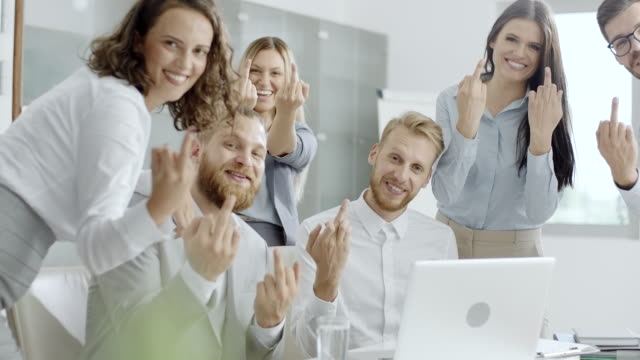 Young coworkers showing middle finger Group of young coworkers showing middle finger in the office and looking at camera. vanity stock videos & royalty-free footage