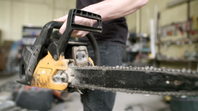 Young Craftsman Starting Powered Chainsaw In Workshop video