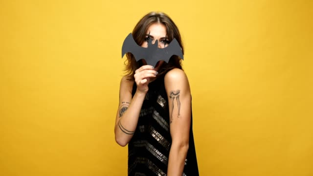 Young crazy brunette woman with haloween make up playing with paper bat isolated over yellow video
