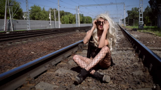 Young crazy woman in black dress and stockings sits alone on rails