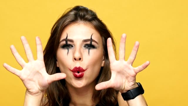 Young crazy woman with creepy make up scaring you and laughing isolated over yellow background video
