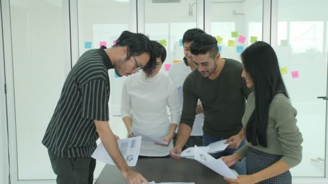 近代的なオフィスにチームワークに関わる新しいアイデア多様なチームの共有をブレーンストーミング若い創造的なビジネス チーム ビデオ