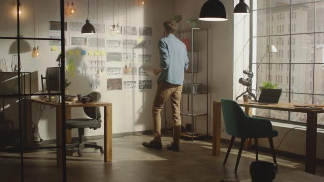 junger kreativer steht neben der wand mit organized mood board in seinem cool loft office. er macht sich notizen zu einem stück papier. sonniger tag vor dem fenster. - storytelling videos stock-videos und b-roll-filmmaterial