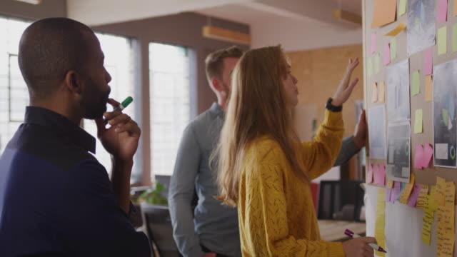 Junge Kreative, die in einem modernen Büro arbeiten – Video