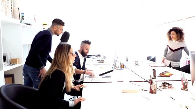 unga kreativa team arbetar med ett projekt på kontoret - kommunikationssätt bildbanksvideor och videomaterial från bakom kulisserna