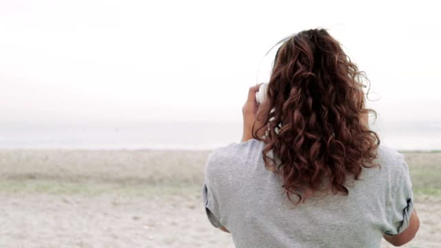 Young curly brunette wears headphones and listens to music on the beach, slow motion, view from the back video