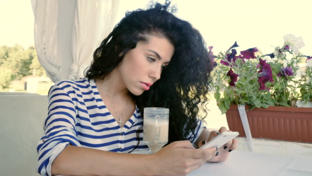Young curly girl is typing a message on phone and relaxing at summer terrace video