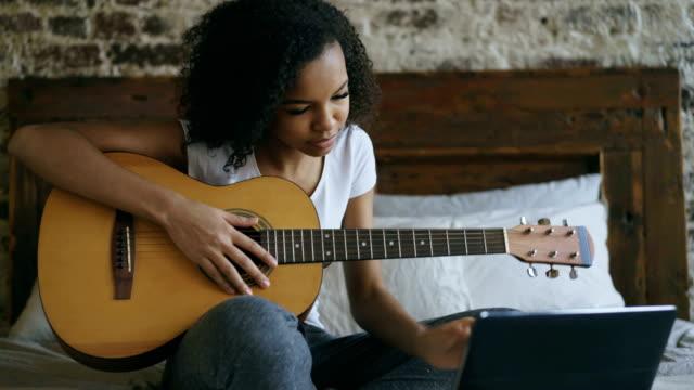 unga lockigt blandad ras tjej concentraing lära sig spela gitarr med hjälp av bärbar dator sitter på sängen hemma - akustisk gitarr bildbanksvideor och videomaterial från bakom kulisserna
