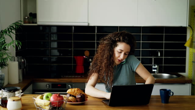 Young curly pretty positive caucasian woman working on laptop and talking on phone sitting in modern kitchen, she is printing and talking in one and the same time video