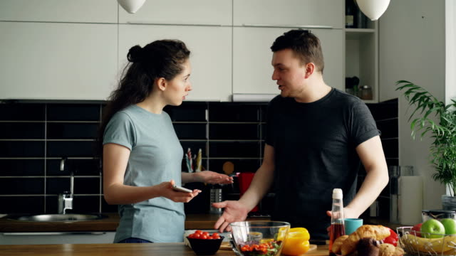 young curly woman showing something unpleasant in husband's phone while he is cooking , they are shouting and quarrelling, man is angry and irritated - walczyć filmów i materiałów b-roll