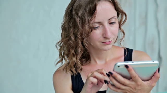 Young curly woman sitting on bed with tablet pc. Dolly shot video