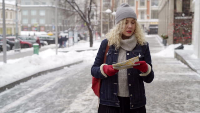 vidéos et rushes de jeune femme frisée, voyageant dans la ville - rouge à lèvres rouge