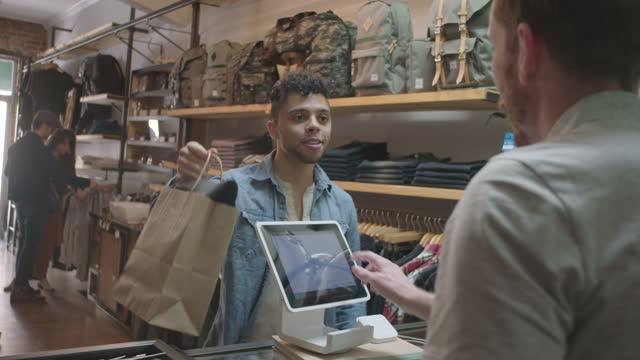 il giovane cliente completa la transazione su tablet e stringe la mano alla cassiera nel moderno negozio di abbigliamento del centro. - comprare video stock e b–roll