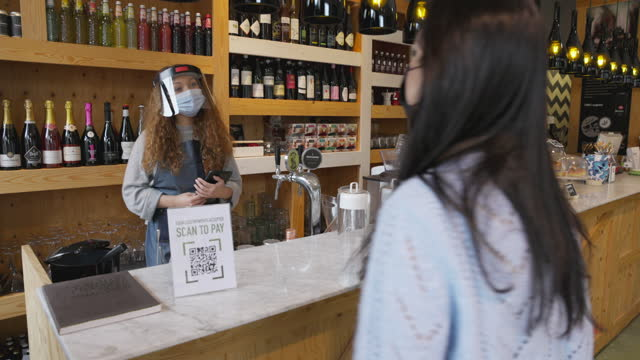 Young customer paying the bill using QR code on mobile phone avoiding contacts video
