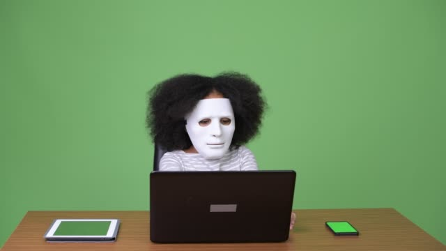 Young cute African girl with Afro hair as hacker using laptop