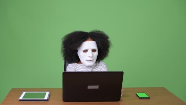vídeos de stock e filmes b-roll de young cute african girl with afro hair as hacker using laptop - mesa mobília