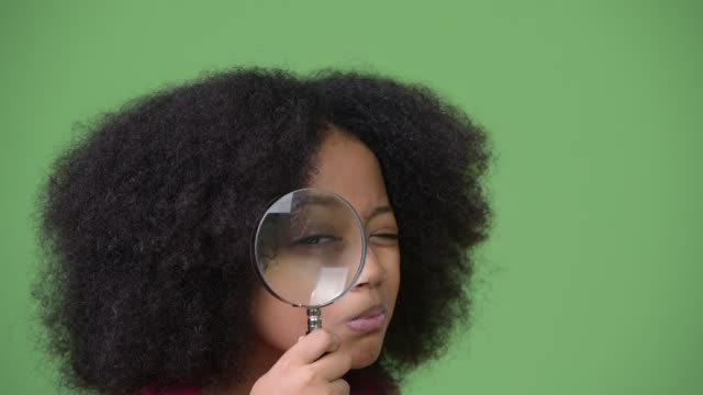 Young cute African girl with Afro hair using magnifying glass Studio shot of young cute African girl with Afro hair against chroma key with green background magnifying glass stock videos & royalty-free footage