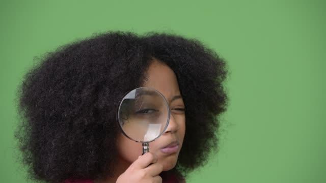 junge süße afrikanische mädchen mit afro-haar mit lupe - lupe stock-videos und b-roll-filmmaterial