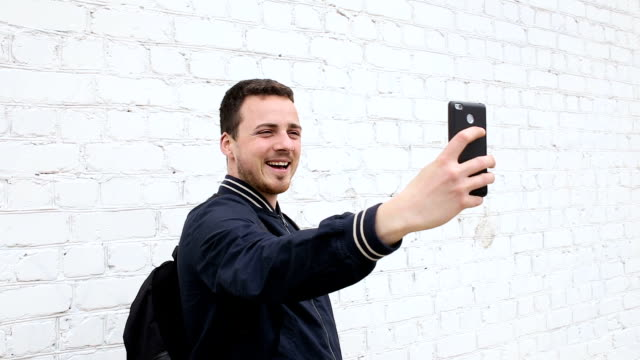Young cute guy doing selfie near white brick wall video