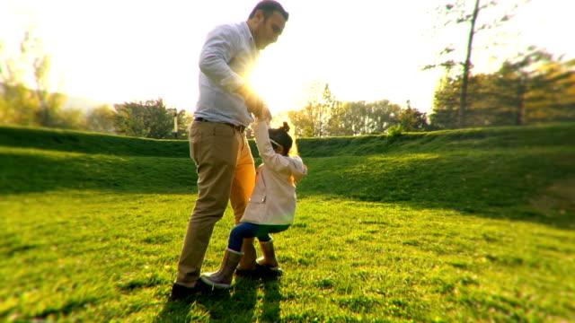 genç baba ve kızı halka açık parkta dans ediyor - babalar günü stok videoları ve detay görüntü çekimi