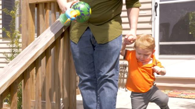 vídeos y material grabado en eventos de stock de un papá joven niño joven hijo mano y le ayuda a caminar por pasos - padre que se queda en casa