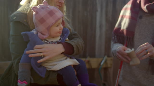 A young dad puts a hat on his baby girl while the mom holds her video