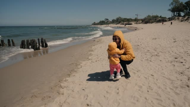 young dad throws up little girl in identical yellow jacket on the sea beach