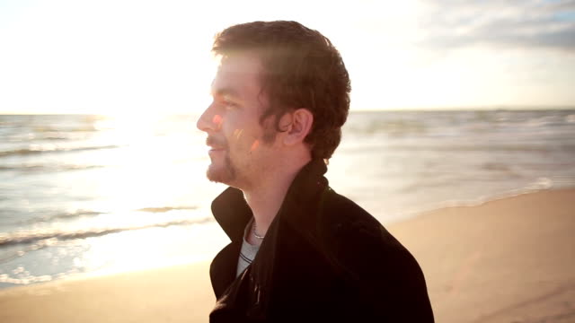 A young dark-haired man in a black coat is walking along the sea shore enjoying the sun rays video