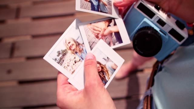 Young daughter holding summer holidays polaroid photos with mother