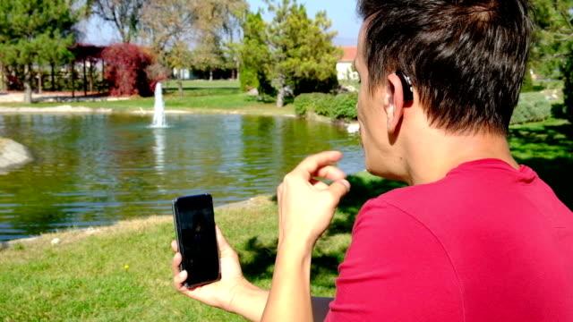 vídeos de stock, filmes e b-roll de jovem rapaz surdo comunicando-se com a língua de sinais no telefone inteligente no parque - surdo