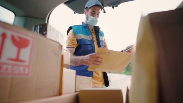 ung leverans man kontrollera leveransadress i bilen bagageutrymmet - posttjänsteman bildbanksvideor och videomaterial från bakom kulisserna