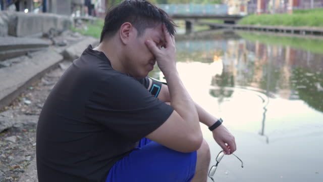Young depressed Asian man sitting on near the pond Depression, sadness, hardship, mental health concepts.