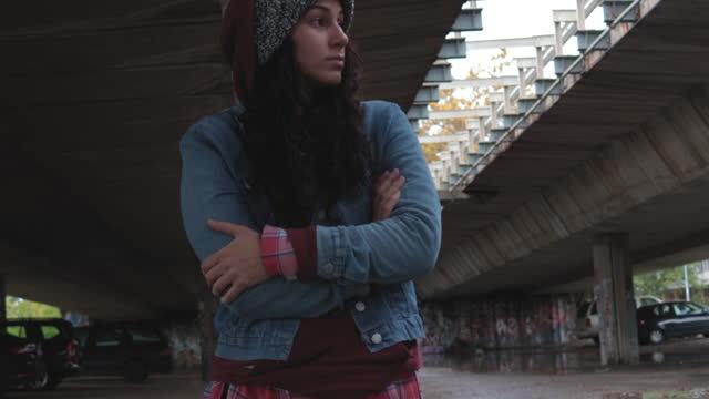 молодая депрессивная бездомная девушка или женщина, стоящая одна под мостом на улице в холодную погоду, чувствуя беспокойство брошенных и � - сбежавший из дома стоковые видео и кадры b-roll
