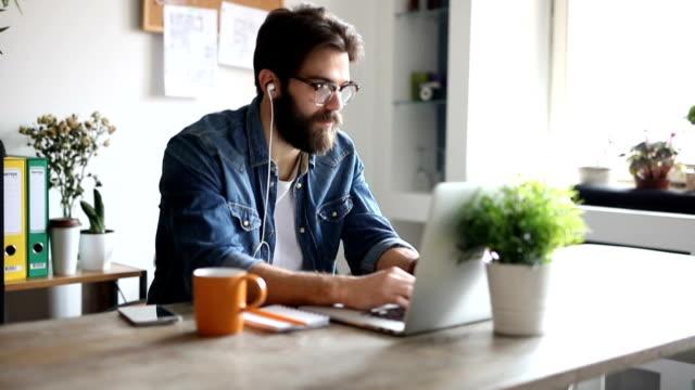 vídeos de stock, filmes e b-roll de jovem designer ouvindo um podcast e trabalhar a partir de seu escritório em casa - trabalho de freelancer