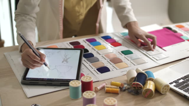 dijital tablet kullanarak moda tasarım stüdyosunda yeni koleksiyon için genç tasarımcı ölçüm ve eşleşen malzemeler - tasarlamak stok videoları ve detay görüntü çekimi