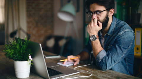 年輕設計師在他的家辦公室舉行視訊會議 - laptop 個影片檔及 b 捲影像