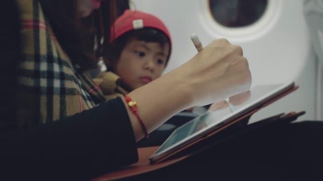 Young designer woman using graphic tablet with her son