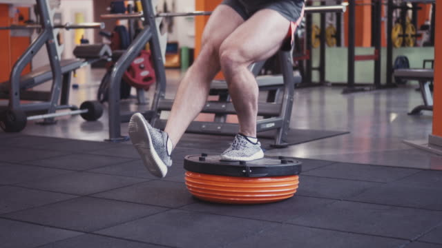 Young determined man doing squats on fitness ball video