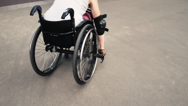 Young determined woman in wheelchair in skate park Generation Z woman in wheelchair practicing stunts in skate park. Determination, courage and confidence shown in this extreme sport done by disabled woman. orthopedic equipment stock videos & royalty-free footage