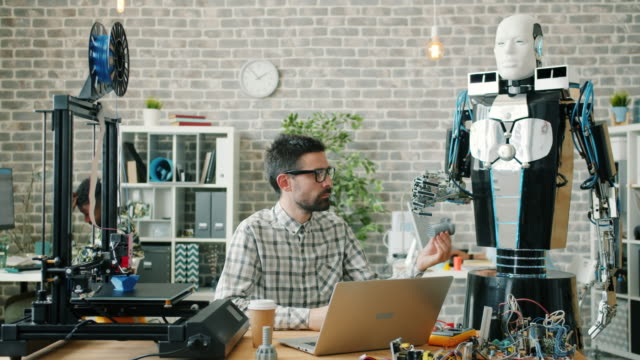Young developer giving 3d printed model to smart robot testing machine in office